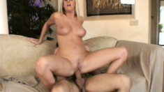 Curvy blonde gets fucked on the couch and takes a big load on her tits