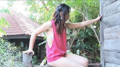 Delightful Asian girl gets fully naked and plays with a dildo outside