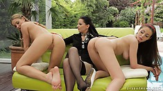 Two sexy babes get it on on the couch while another supervises