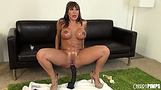 Busty bitch Ava Devine glistens with oil during a kinky show