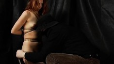 Redhead is tied up and one leg is pulled in the air to show her twat
